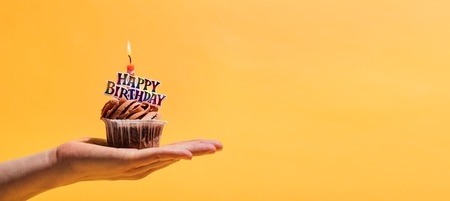 Womans hand holding decorated birthday muffin against yellow background. Birthday party and celebration.