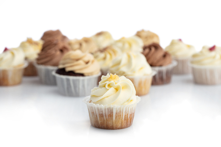 Frosted lemon cupcake in a close-up. Blurred muffins in the background. Sweet treat. Dessert. Stock Photo