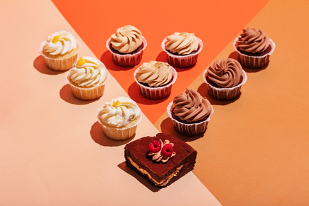 Cupcake and piece of cake in a colorful geometrical composition. Tasty sweet treats. Top view.