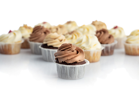 Frosted chocolate cupcake in a close-up. Blurred muffins in the background. Sweet treat. Dessert. Stock Photo