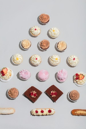 Different desserts composed in triangular shape on grey background. Top view, flat lay. Stock Photo