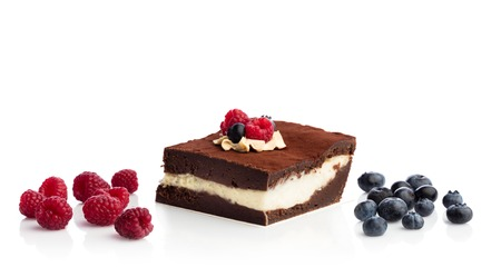 Piece of chocolate cake and seasonal fruits isolated on white background. Sweet dessert. Stock Photo