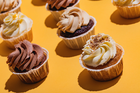 Cupcakes standing on yellow background in a close-up. Delicious treat.