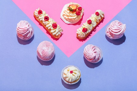 Sweet desserts in a pastel triangular composition. Delicious cakes. Flat lay. Stock Photo