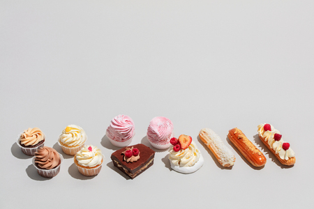 Sweet dessert composed in two rows on grey background. Sweet pastry. Flat lay, copyspace.