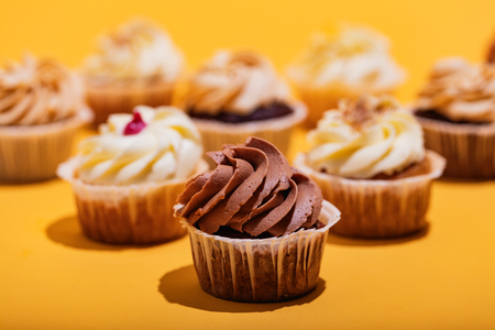 Chocolate muffin in a close-up on yellow background. Sweet cupcakes. Dessert.
