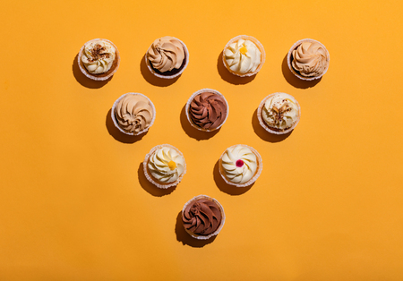 Tasty muffin in composed triangular shape on yellow background. Flat lay. Yummy dessert.