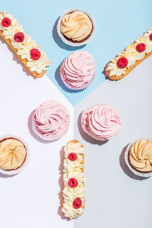 Tasty cakes in a pastel flat lay composition. Eclairs and muffins. Sweet food.