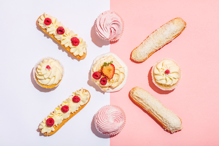 Bunch of sweet cakes in a pastel geometrical composition. Flat lay. Colorful decorated desserts.