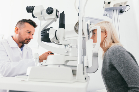Optician checking woman's eyesight with special equipment. Medicine, healthcare. Archivio Fotografico