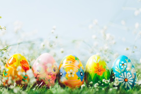 Decorative eggs on green grass. Easter, traditioonal Christian spring holiday. Copyspace.