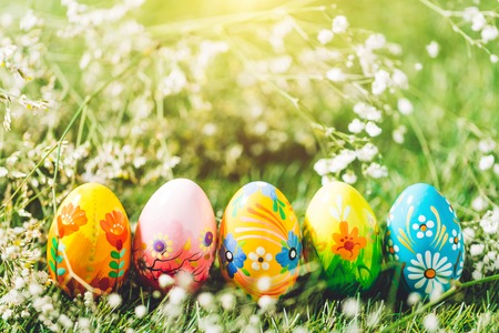 Five Easter eggs on green grass. Colorful traditional decoration, spring holiday. Stock Photo