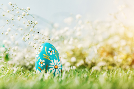 Colorful Easter egg on the green grass. Christian holiday, traditional decorative symbol.