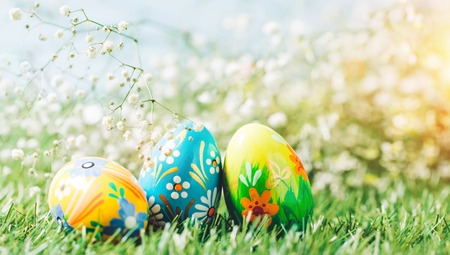 Easter eggs on the green meadow. Christian holiday, traditional decorative symbol. Stock Photo