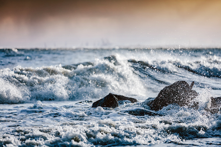 Storm on the sea, waves hitting rocks. Dangerous weather, natural phenomenon. Baltic Sea in Gdynia, Poland.