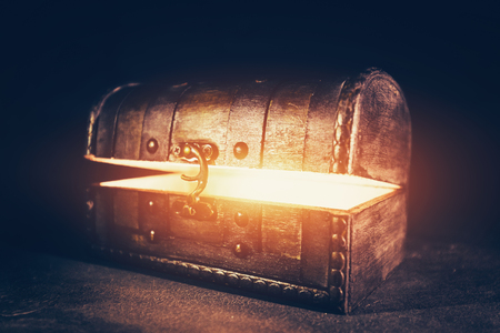 Magic wooden box with glowing light. Ancient mysterious chest. Precious antique box.