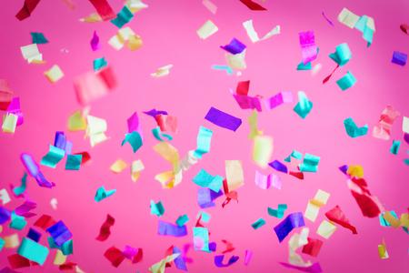 Falling confetti on pink background. Party, birthday celebration. Colorful festive background.