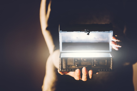 Woman holding old treasure box with glowing light. Mystery and magic. Secret content. Stock Photo