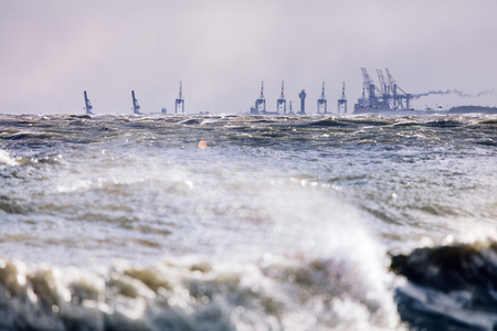 Stormy sea and industrial landscape in the background. Gdynia, Poland, Baltic Sea.