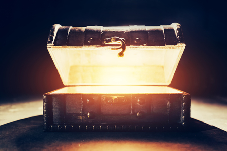 Ancient wooden box with glowing light. Open chest with treasures inside. Stock Photo