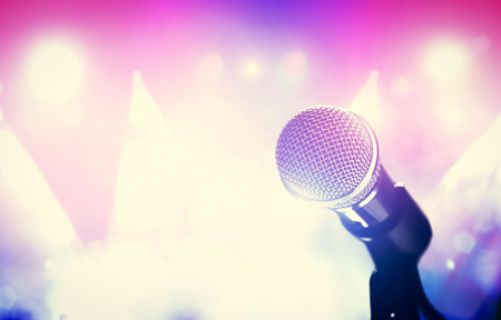 Microphone and bright colorful stage lights. Concert, music show, gig. Singing performance. Stock Photo