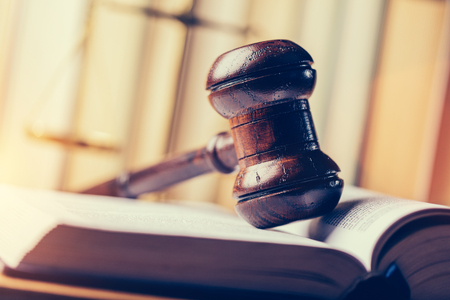 Court hammer laying on book. Justice, trial and law symbol. Judgment. Stock Photo