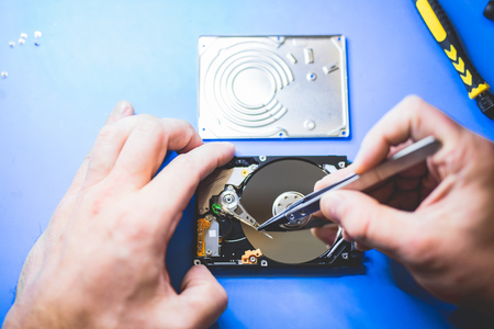 Man fixing a hard disc. IT engineering and hardware. Professional service. Technology.