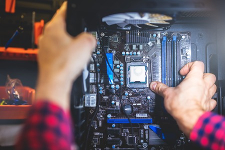 IT service and man fixing a PC in a workshop. Professional worker. Modern technology. Stock Photo