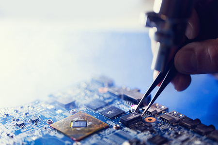 Man putting microchip on the CPU board. IT technologies, professional service and workshop. Stock Photo