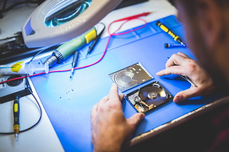 Worker inspecting hard drive in workshop. Professional IT service. PC hardware.