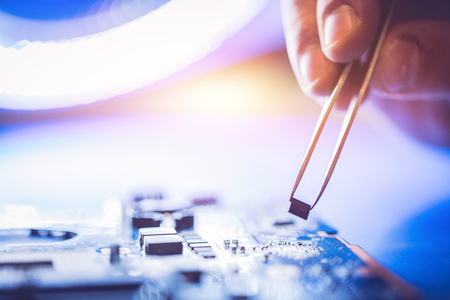 Microchip installed on the main board. IT service, technology engineering. Stock Photo
