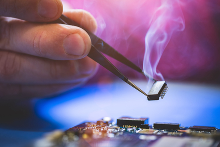 Man holding smoking chip over the computer CPU board. IT technology, fixing electronical devices. Stock Photo