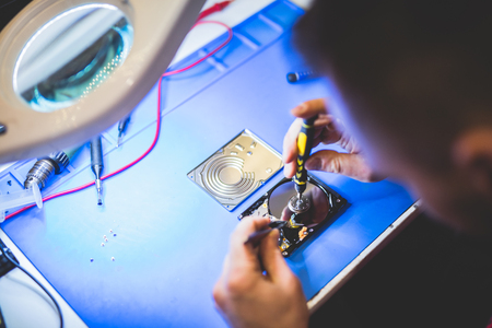 Man repairing a hard disc in workshop. Professional IT service. Technology.