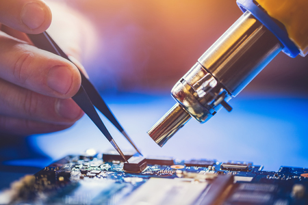 Serviceman installing microchip on main board if a computer. IT specialist fixing electronical devices. Stock Photo