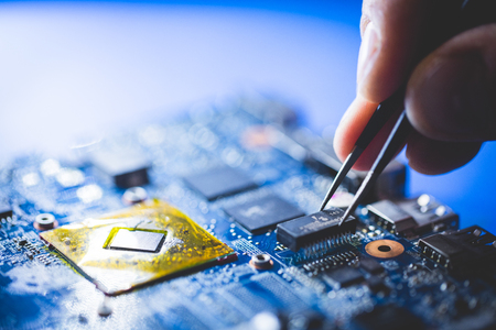 Microchip installation on CPU board. Professional IT service. Modern technologies and engineering.