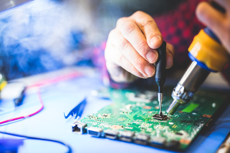 Worker fixing a main board of a computer. IT engineering. Modern electronic devices.