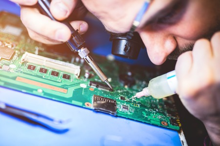 IT worker repairing main board of a computer. Professional technical service. Technology.
