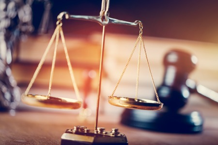 Symbols of law - gold measuring scales and courtroom gavel. Justice and trial concept.