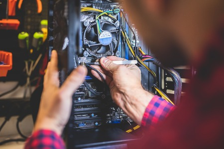 Man fixing PC in professional workshop. IT service and engineering. Electronical device.