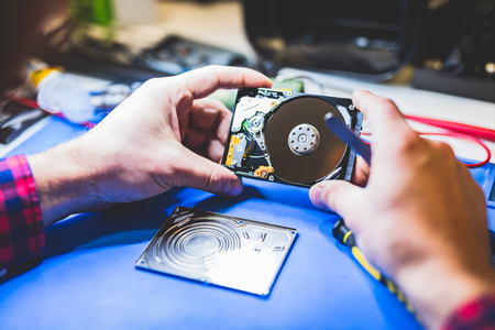 Man holding a hard disc. IT hardware. Engineering and technical service.