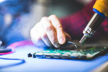 Worker fixing CPU board of a computer. Hardware, IT engineering. Professional service. Stock Photo