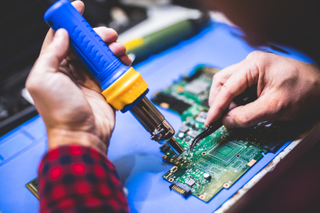 Man fixing main board of a computer. IT specialist, engineering. Technology.
