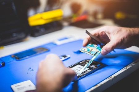 Man fixing broken phone. Professional service, electronical devices reparation.