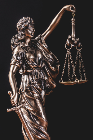 Themis statue holding a scale on black background. Symbol of law, justice and order.
