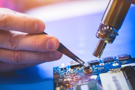 Man installing a chip on CPU board. Computer service, IT specialist.
