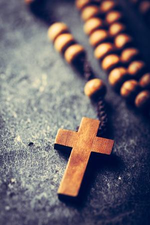 Kruis en rozenkrans op stenen achtergrond. Katholieke kerk, religieus symbool. Gebed. Stockfoto