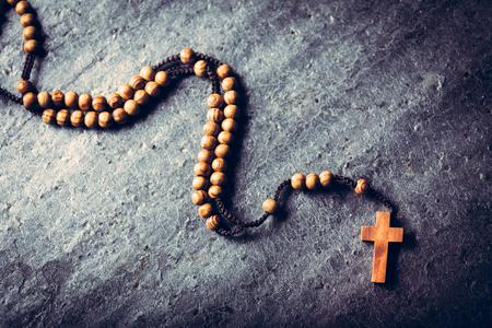 Wooden rosary laying on stone background. Catholic church, religious symbol. Prayer.