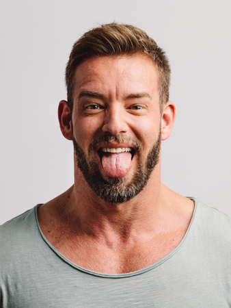 Handsome man sticking his tongue out making faces. Close-up casual portrait