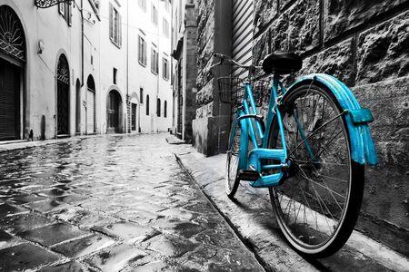 Retro blaues Fahrrad auf der Altstadtstraße. Farbe gegen Schwarzweiß. Vintage-Stil. Florenz, Italien