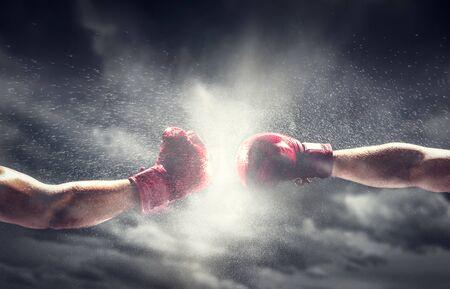 Un pugno di due guantoni da boxe. Luce sul cielo nuvoloso. Scatola, potere, simboli di combattimento.
